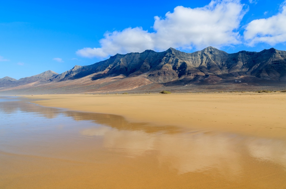 'Reflection of mountains in wet sand on Cofete beach in secluded part of Fuerteventura, Canary Islands, Spain' - Kanariansaaret